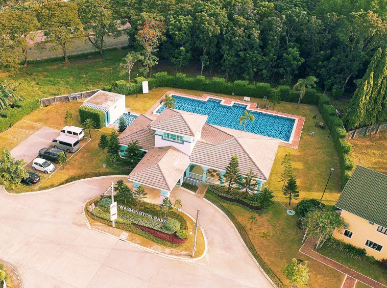 Camella Savannah clubhouse and swimming pool with parking lot surrounded by tall trees